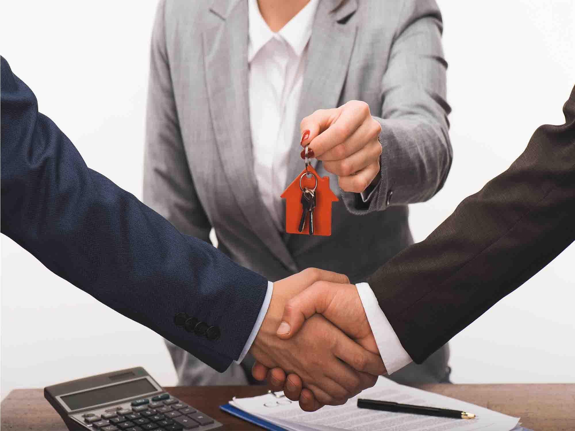 שני אנשים לוחצים ידיים ומקבלים מפתח ממישהו