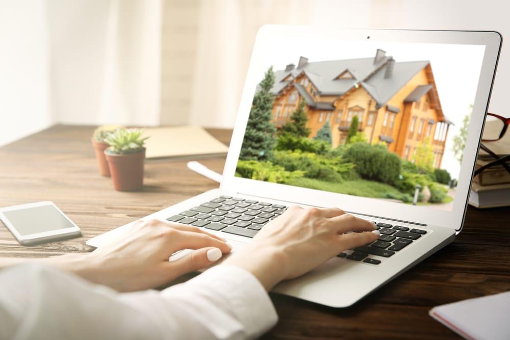 אשה מקלידה על מחשב נייד שבצג מופיע בית